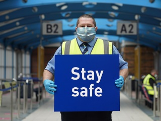 Interchange member of staff with sign saying ' Stay Safe'